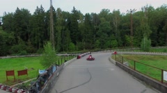 Two sportsmen drive in carts by bridge on racing track at summer Stock Footage