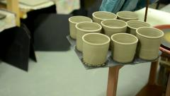 Woman puts the finished cup to other cups - all same - detail Stock Footage