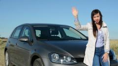 Young attractive happy woman waves in greeting - smile - eye contact - car Stock Footage