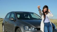 Young attractive happy woman rejoices in the successes - she stands by the car  Stock Footage