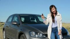 Young attractive happy woman holds key of new car - she is absolutely satisfied  Stock Footage