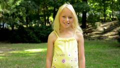 little happy girl stands in the park and smiles - eye contact - stock footage