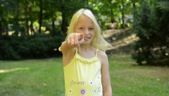 little young happy girl stands in the park and shows on you with finger - nod  - stock footage