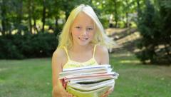 Little cute happy girl stands in the park and holds books - she looking forward  Stock Footage