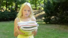 Little girl holds many books in the park - she is tired because she has to much  Stock Footage