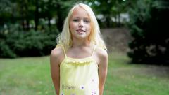 Little girl with arms behind the back, tells something to the camera  Stock Footage