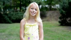 Little cute smiling girl nods her head - agree - she stands in the park Stock Footage