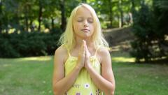 Little cute girl prays in the park with prayer hands together - closed eye Stock Footage