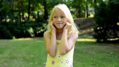 Little upset girl covers her ears with fingers in the park - annoyed Stock Footage