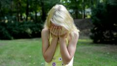 little sad girl cry in the park - she covers her face with hands - stock footage