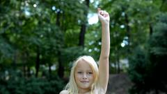 Little lively girl puts hand up and shake it - in the park - knowledge  Stock Footage