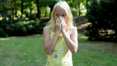 Little cute girl blows her nose in the park - sneezing - allergy Stock Footage