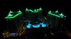 Illuminated edifices and pool of Azura Park hotel at night. Stock Footage