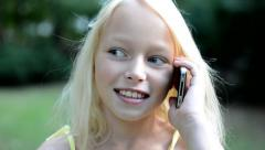 Little happy girl call with friend on the phone in the park - talking  Stock Footage