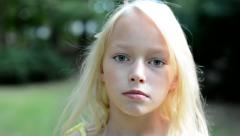 little beautiful girl gaze in the camera in the park - close up - stock footage