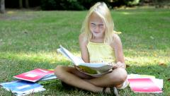 Little cute smart girl sits in the park with many workbooks - she enjoy study Stock Footage