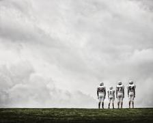 A group of four football players in sports uniform - stock photo