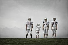 A group of four football players in sports uniform, - stock photo