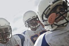A group of football players, young people in protective helmets. Stock Photos
