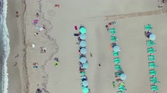 Tourists get rest on beach with sunbeds and parasols at summer Stock Footage