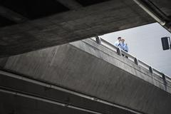 Two businessmen standing leaning on a railing on a city walkway - stock photo