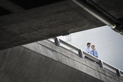 Two businessmen standing leaning on a railing on a city walkway Stock Photos