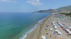 Sand beach with many tourists at summer sunny day. Stock Footage