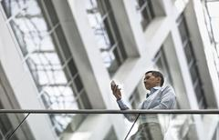 A man checking his smart phone in a large airy building with windows. - stock photo