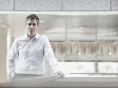 A man in a white shirt with an open collar, in a large airy building. - stock photo