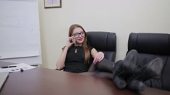 Businesswoman sitting with legs on desk Stock Footage