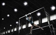 A gymnast, a young woman performing a routine on the parrallel bars. - stock photo