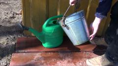 Gardener pouring water into green plastic watering can - stock footage
