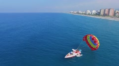 People change cutter with parachute to inflatable boat near beach Stock Footage