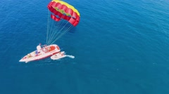 Inflatable boat rides from cutter with parachute at summer Stock Footage