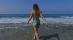 Woman in swimwear walks and sits in sea waves at summer sunny day. Aerial view Stock Footage
