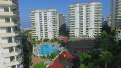 Pool and tennis courts among residential buildings at summer Stock Footage
