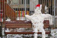 Handmade snowman with red hat made from natural snow - stock photo
