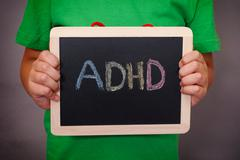 Young boy holds ADHD text written on blackboard Stock Photos