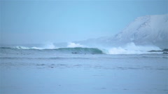 Arctic surfers in water Grotta Reykjavik Iceland winter big waves mountains Stock Footage