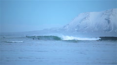 Arctic surfer Grotta Reykjavik Iceland winter big waves snowy mountains Stock Footage