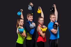 Group Of Sporty People With Kettlebells Isolated On Gray Background - stock photo