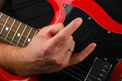 Hand with red guitar and devil horns isolated on black - stock photo