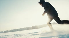 Athlete woman is running during winter training outside in cold snow weather. Arkistovideo