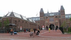 People ride bicycles in front of the Rijksmuseum in Amsterdam, Netherlands. Stock Footage