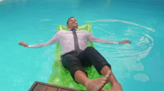 Businessman relaxing on lilo Stock Footage