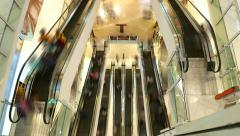 Several escalators from top, smooth people figures rush around, time lapse shot Stock Footage