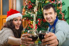 Couple at Christmas time making toast with glasses of wine - stock photo