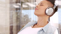 Happy pregnant woman listening to musing and putting headphones on her belly Stock Footage
