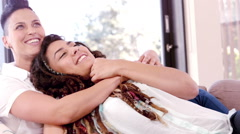 Lesbian couple chilling on sofa together - stock footage