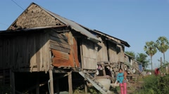 Woman with child walking past poor wooden houses,Kratie,Cambodia Stock Footage